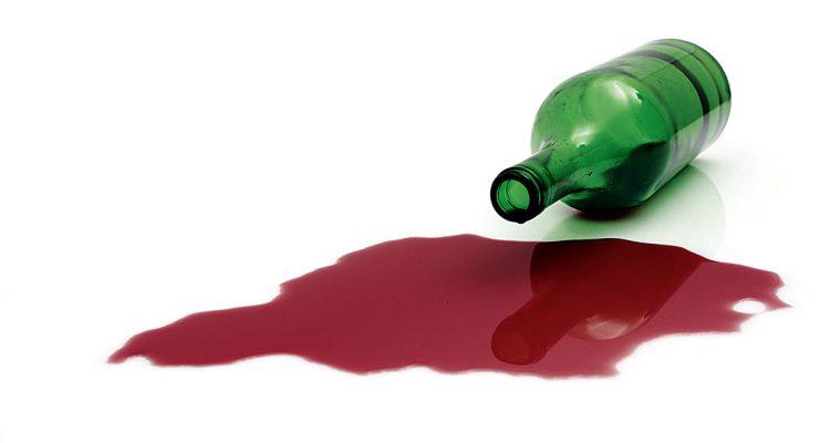 Ausgelaufene Weinflasche auf weiss